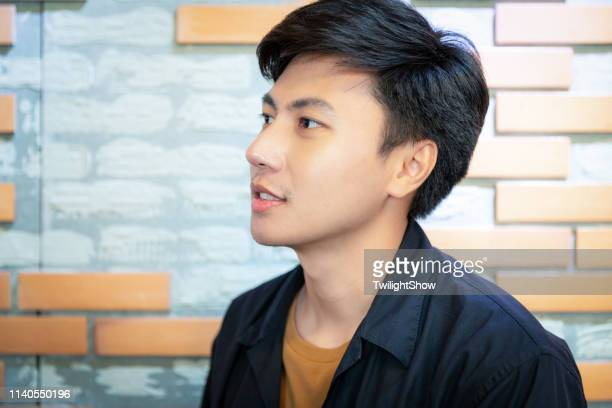 young confidence handsome asian man standing looking at camera - thai ethnicity stock pictures, royalty-free photos & images