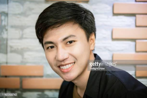 カメラを見て立っている若い自信ハンサムなアジアの男 - タイ人 ストックフォトと画像