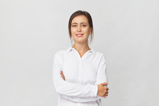 Young confident brunette woman in white elegant shirt smiling portrait against white background 1064924442