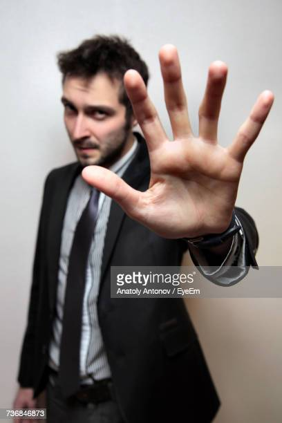 Young Confident Businessman Showing Palm Against Wall