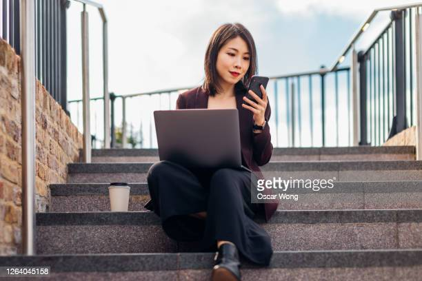 young confident businesswoman using smart phone while working with laptop on staircases - using laptop stock pictures, royalty-free photos & images