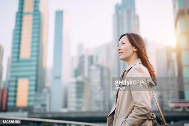 Young confident corporate woman looking at city view on urban balcony