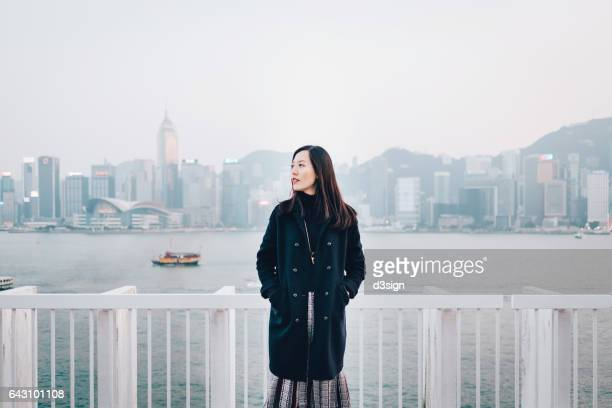 Young confident lady standing against urban city skyline