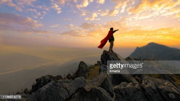 young confident man look beyond and wearing red cape acting like a superhero on top of the mountain. imagining of successful concept. - superhero stock pictures, royalty-free photos & images