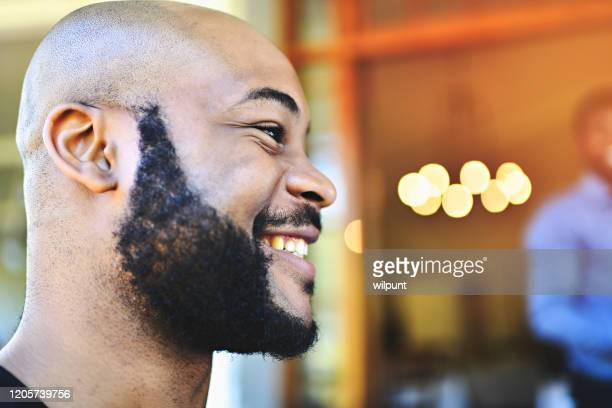 young confident man with beard side view portrait smiling - 20 29 years stock pictures, royalty-free photos & images