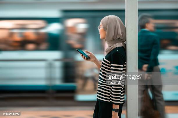 young confident muslim woman using phone while waiting for train. - islam stock pictures, royalty-free photos & images