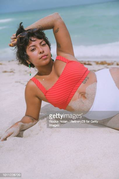 Young confident woman laying on the beach