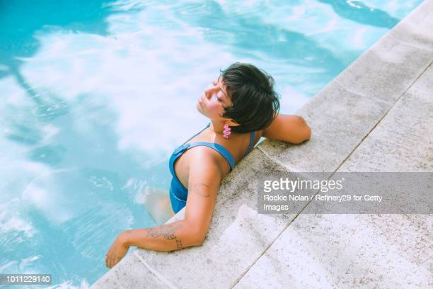 young confident woman relaxing in a pool - noapologiescollection stock pictures, royalty-free photos & images