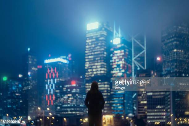 Young confident woman standing against urban cityscape and looking away