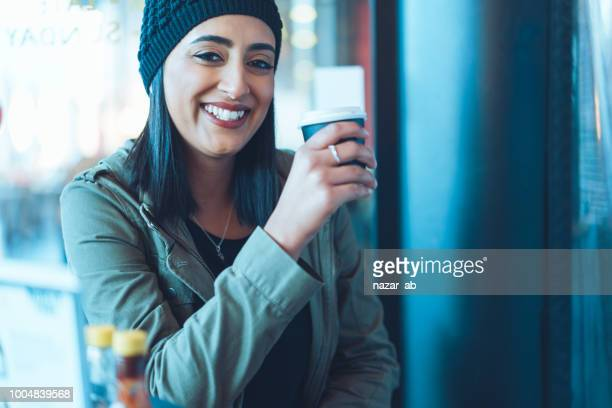young confident woman with smile having coffee. - one young woman only stock pictures, royalty-free photos & images