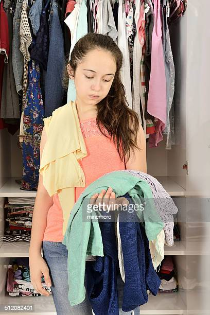Young confused girl standing in front of a wardrobe