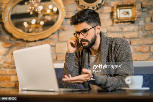 young confused man looking at his laptop . - computer virus stock pictures, royalty-free photos & images