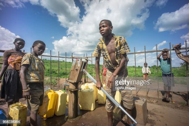 A young congolese refugee seen getting water for his family at one of the water pump system for underground water at the Kyangwali refugee camp...