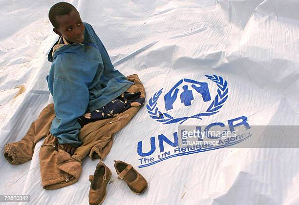 Young Congolese refugee sits on a plastic sheeting donated by the United Nations refugee agency UNHCR to be used as a tent for refugees at the...