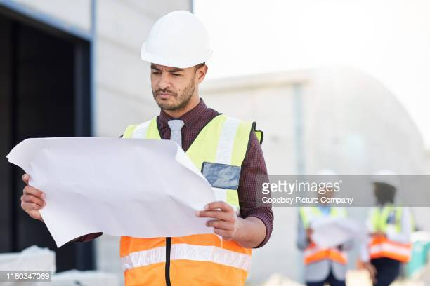 young construction engineer going over blueprints on a building site - real estate developer stock pictures, royalty-free photos & images
