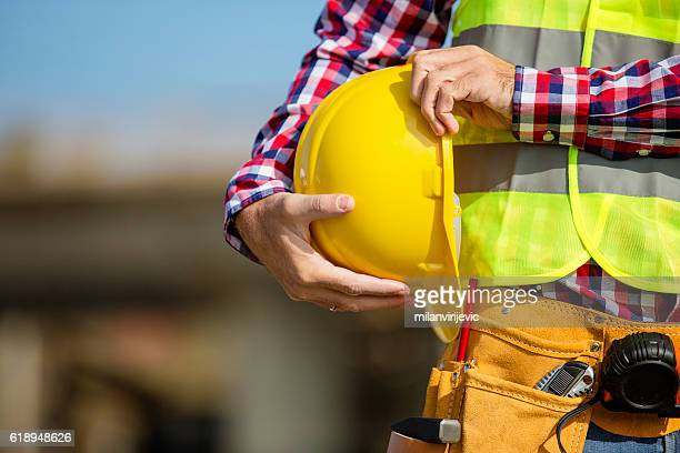 young construction worker holding a yellow helmet - risques liés à une activité photos et images de collection