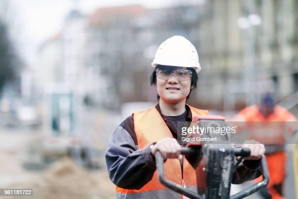 young construction worker wearing hard hat - sigrid gombert stock-fotos und bilder
