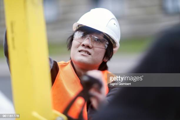 young construction worker wearing hard hat - sigrid gombert imagens e fotografias de stock