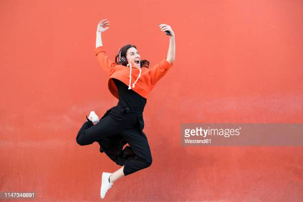 young contemporary dancer jumping and using smartphone in front of a red wall - human arm stock-fotos und bilder