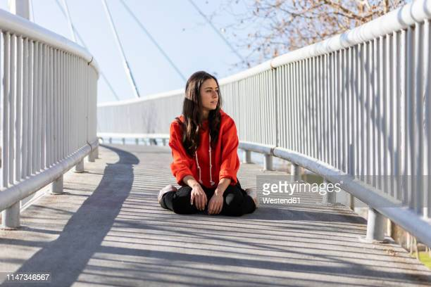 young contemporary dancer sitting on a footbridge - 人工建造物 ストックフォトと画像