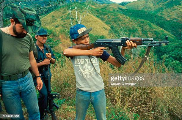 A young contra fighter receives firearms training at a remote jungle base camp inside Honduras His issued weapon is the ubiquitous AK47 which he is...