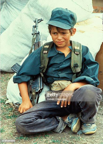 A young contra fighter rests against sacks of rice at a Honduran base camp near the Nicaraguan border The youth is armed with an AK47 equipped with a...