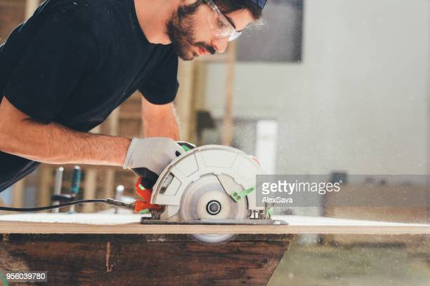 young contractor precisely cutting a piece of wood - circular saw stock photos and pictures