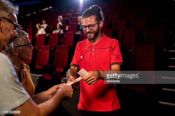 junger controller im kino prüft die eintrittskarten für zuschauer - premiere stock-fotos und bilder