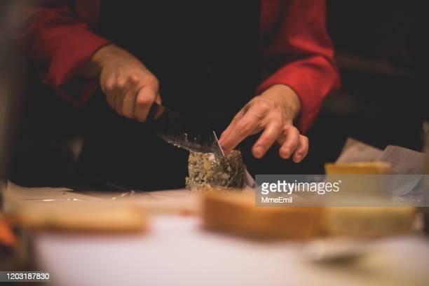 jonge kok die blauwe kaas snijdt - blauwschimmelkaas stockfoto's en -beelden