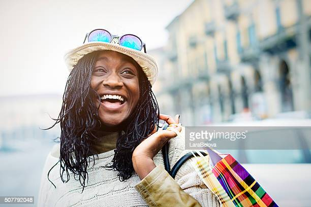 Young cool African woman with shopping bags on the street