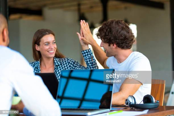 Young cooleagues working together in start up company, giving high five