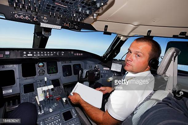 Young co-pilot at work in a cabin of commercial jet