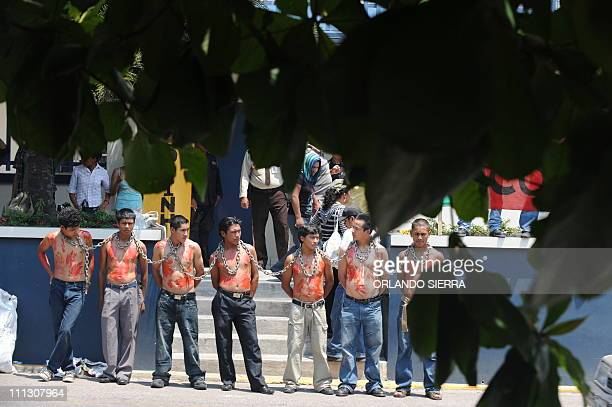 Young COPINH indigenous organization activists keep themselves chained up together in front of the UN bulding in Tegucigalpa on March 31 protesting...