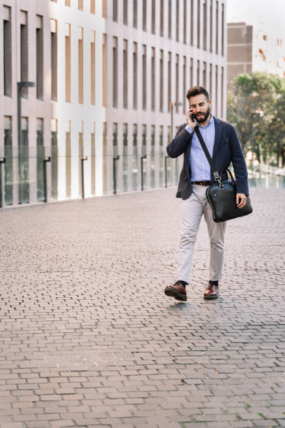 Young corporate businessman having phone call and walking on street of modern business area