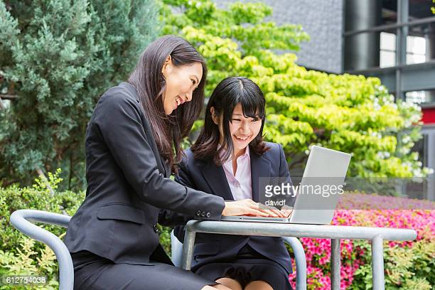 Young Corporate Japanese Business Women Working Outdoors With Computer