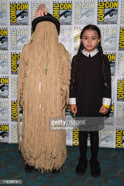 """Young cosplayers Ron Pizarro and Mya Pizarro dressed as Cousin It and Wednesday Addams from """"The Addams Family"""" at 2019 Comic-Con International at..."""