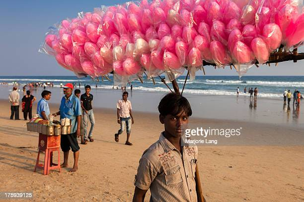 CONTENT] Young cotton candy seller walking on Puri beach during Indian holidays Orissa India
