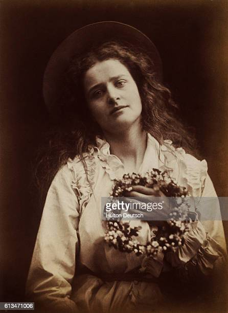 A young countrywoman with a garland of flowers The photograph titled The Queen of the May by the early English photographer Julia Margaret Cameron...
