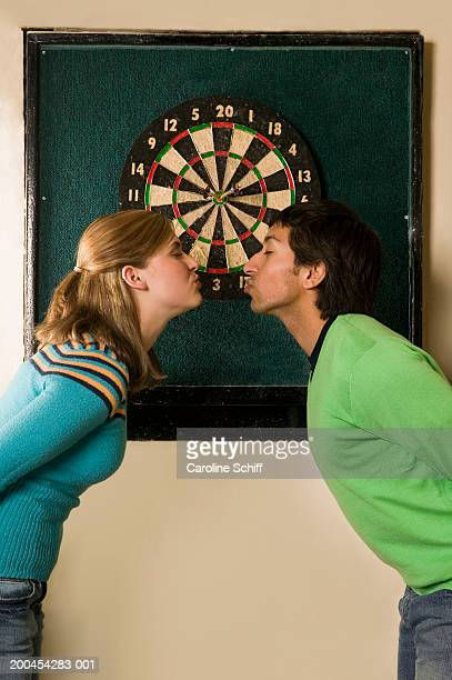 young couple about to kiss in front of dartboard, side view - schiff stock photos and pictures