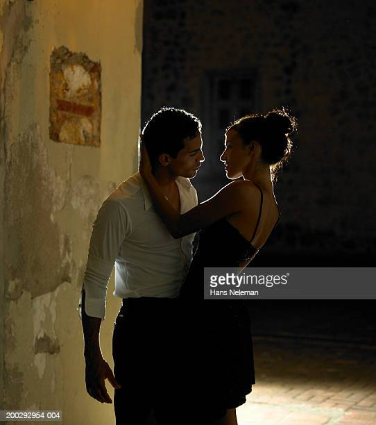 Young couple about to kiss in square at night