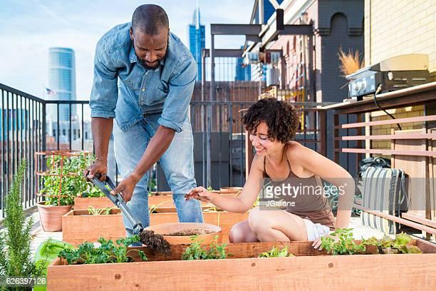Young couple adding soil to a planter box
