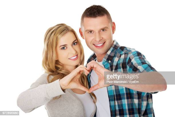 young couple against white background - gesturing stock pictures, royalty-free photos & images