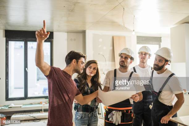 Young couple analyzing blueprints with team of manual workers.