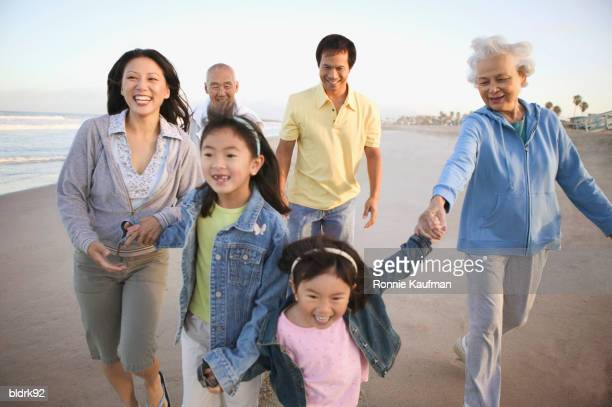 Young couple and a senior couple walking on the beach with children