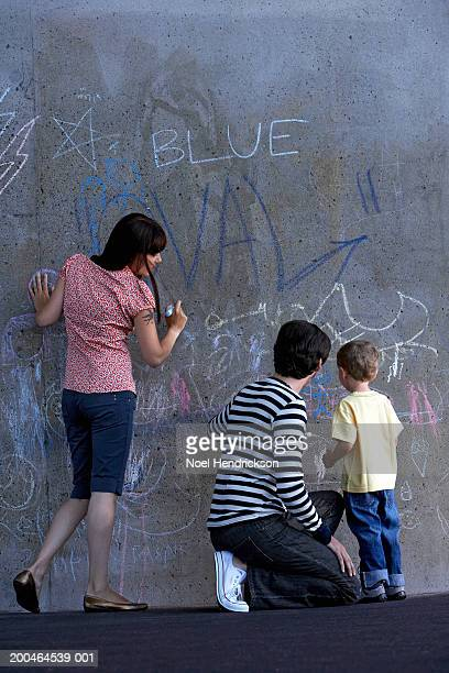 young couple and boy (2-4), drawing on wall with chalk, rear view - chalk wall stock pictures, royalty-free photos & images