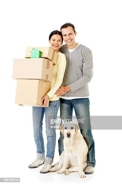 Young couple and dog holding moving boxes