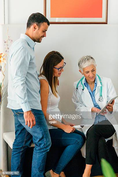 young couple and female doctor in a consultation. - frauenarzt untersuchung stock-fotos und bilder