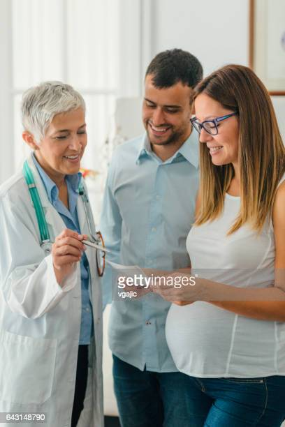young couple and female doctor in a consultation - human fertility stock pictures, royalty-free photos & images
