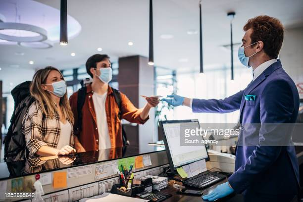 young couple and male receptionist with protective face masks at the hotel reception - hotel stock pictures, royalty-free photos & images