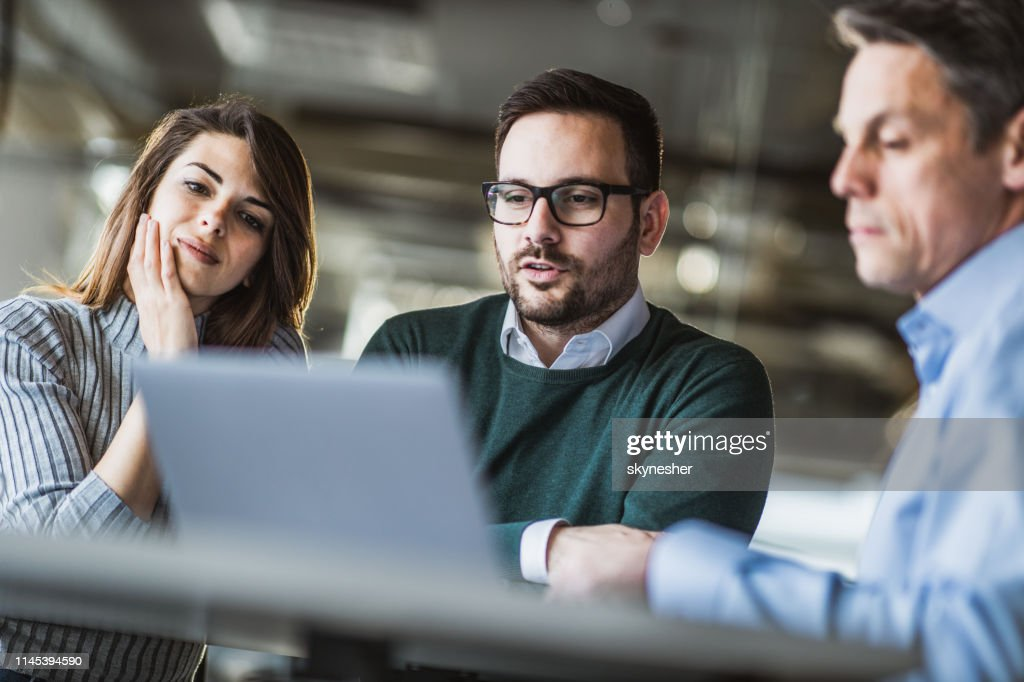 Young couple and real estate agent using laptop on a meeting in the office. : Foto stock